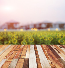 look at wooden desk over blurred sunflower and house.