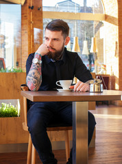 Guy with tattoos drinking coffee.