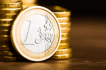 one euro coin and gold money on the desk