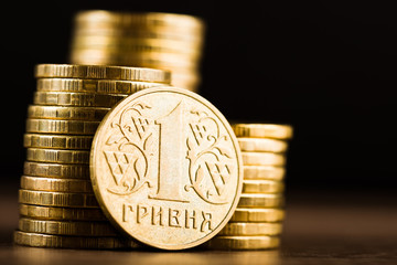 Ukrainian one hryvnia coin and gold money on the desk