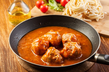 Meatballs with tomato sauce on black pan
