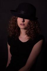 Low key portrait of beautiful girl in black hat