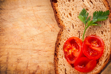 fresh rye bread and tomato on wooden background