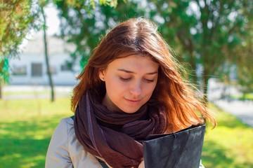 Портрет красивой девушки в парке с папкой в руках