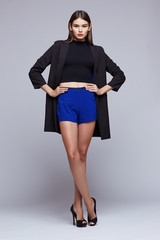 young elegant woman in blue shorts, black jacket. Fashion studio