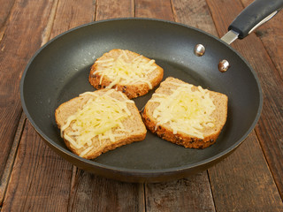 Photo of a grilled cheese sandwich cooking in a large frying pan