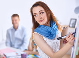 Young woman drawing on wihteboard with white copyspace