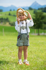 Smiling little bavarian boy holding a pretzel in hands