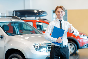 Young smiling salesman with clipboard in car dealership