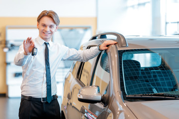 Sales man holds keys from a new car