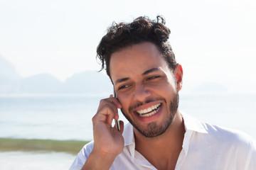 Lachender Brasilianer mit Telefon an der Copacabana
