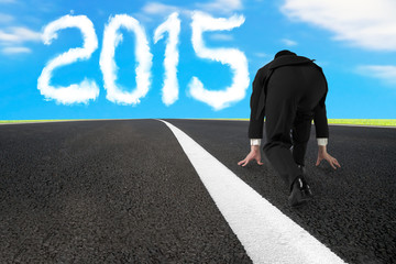 Businessman ready to run on asphalt road with 2015 cloud