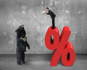 Businessman using megaphone yelling at black bear on percentage
