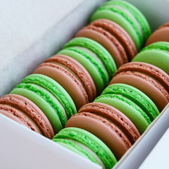Set of pistachio and caramel macaroon in white box, square
