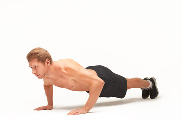 Muscular shirtless sportsman making push-ups on palms in studio