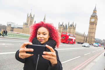 Girl taking selfie in London with Big Ben on background