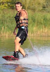 Happy handsome man wakesurfing