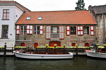 Boats on the canal near the house with shutters