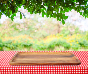 Empty wooden tray on table over blur trees with bokeh background