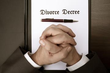 Male hands crossed over Divorce Decree documentation