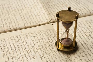 hourglass and handwritten document