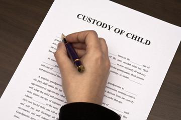Female hand filling custody of child form
