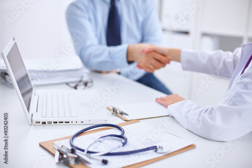 Doctor and Patient sitting on the desk плакат