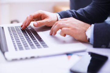 Businessman sitting at table with laptop and documents