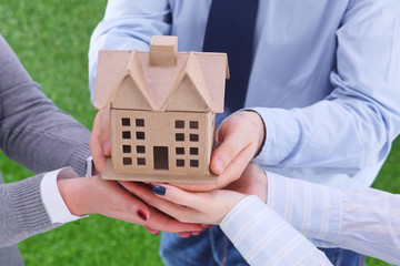 Group of businesspeople holding model house