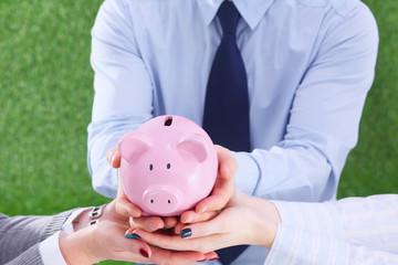 Businesswoman and man holding a piggy bank