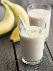 Healthy banana smoothie on wooden background