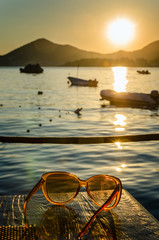 Sunglasses on wooden table at sunset