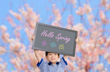 "Little Asian boy holding chalkboard with message ""Hello Spring"""