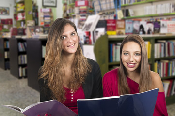 two young smiling girls studying in the library