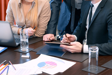 Business partners use tablet at the meeting