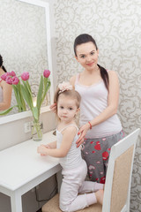 Mother and daughter near mirror