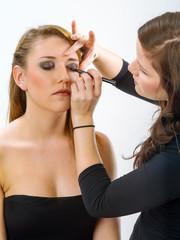Makeup artist applying makeup on model
