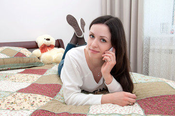 Young girl lying on the bed and talking on a mobile phone