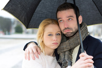 Portrait of a young couple on holidays under the rain