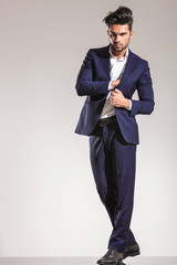Young business man standing and pulling his coat