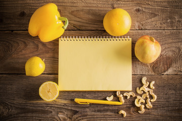 Yellow fruits and vegetables on wooden background
