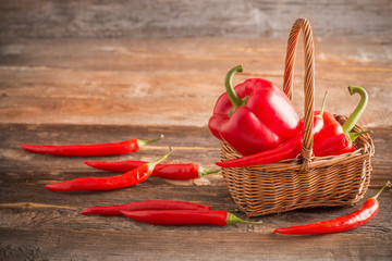 red chili peppers in basket  on old wooden table