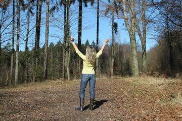 Frau genießt Freiheit im Wald im Frühling