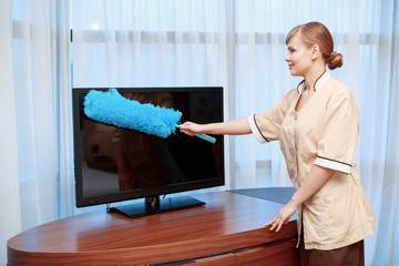 Hotel maid dusting furniture