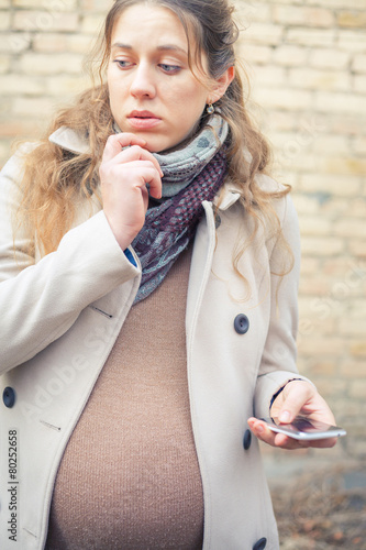 Poster pregnant woman calling by mobile phone