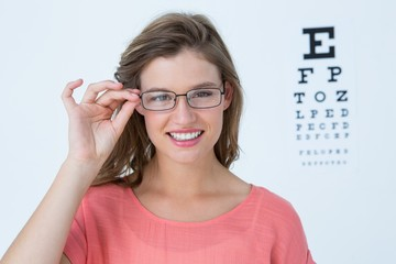Hipster with eyeglasses and eyes test behind her