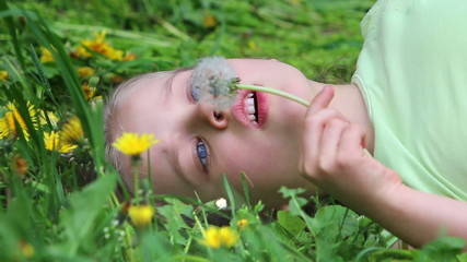 Child girl lying in grass and blowing on dandelion.