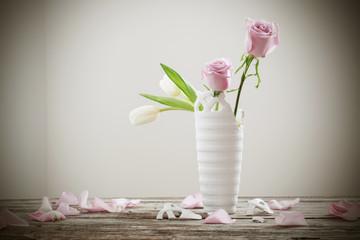 pink roses in broken flower vase on old wooden table
