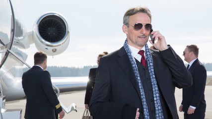 executive manager in front of corporate jet using a smartphone
