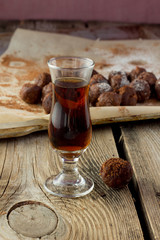 Small glass of brandy and homemade candies on wooden table